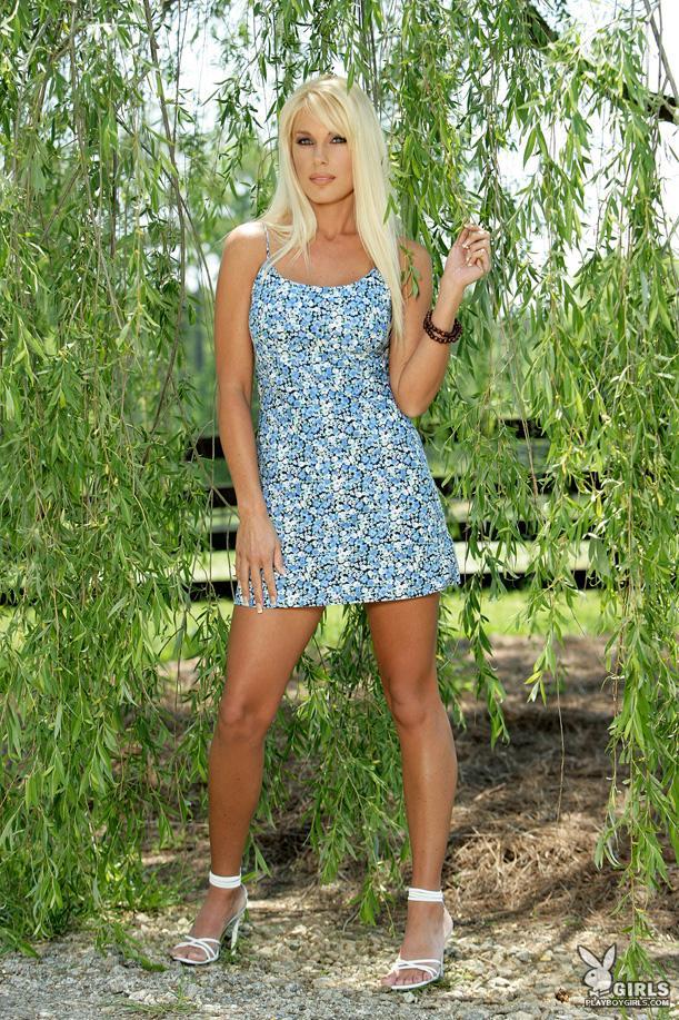Титястая модель со свелыми волосами Angel Barber стягивает голубое платье в тени дерева