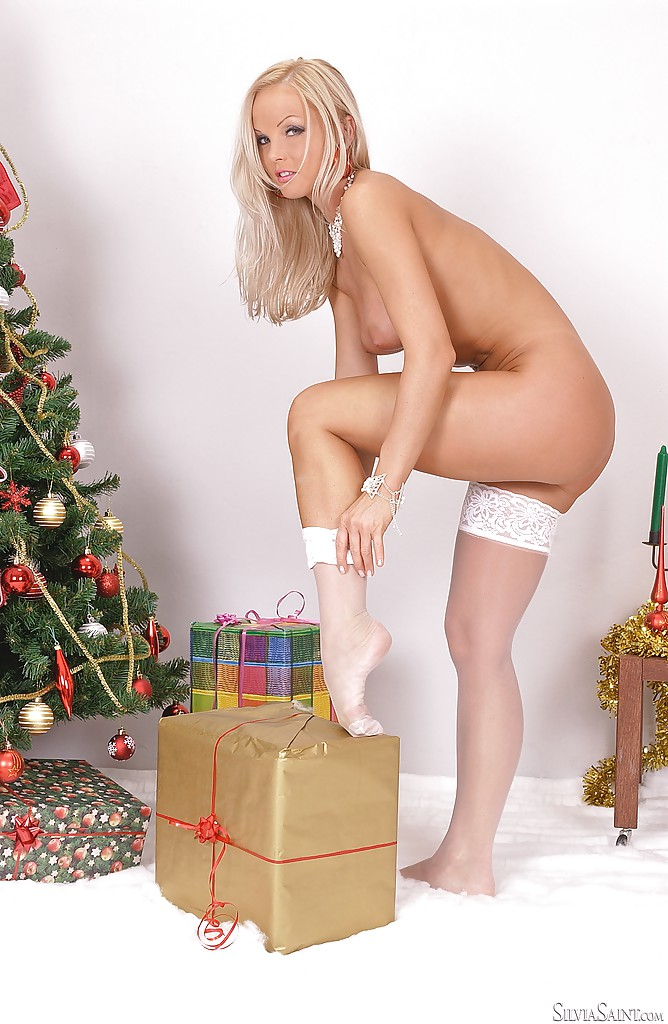 Приятная блондиночка снимает одежду под елкой